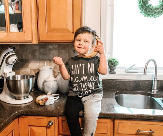 child sitting on kitchen counter baking and playing in the kitchen